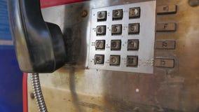 För löntelefon för gammal teknologi gammalt bås med den fysiska landlinjen kommunikation, tryckknapptelefon, fortfarande aktiv i  arkivfilmer