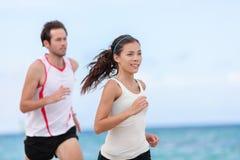 För löparepar för kondition mellan skilda raser spring på stranden fotografering för bildbyråer