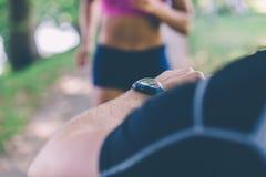 för löparetajming för kvinnlig personlig instruktör Selektivt fokusera royaltyfri bild