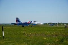 För lag` för strålen SU-27 adlar aerobatic ryss `-ställningar på landningsbanan av flygplatsen Royaltyfri Foto