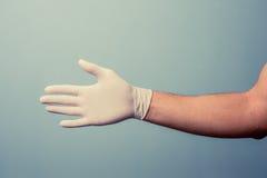 För latexhandske för hand bärande erbjudande handskakning fotografering för bildbyråer