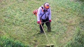 För lawnmoverman för bästa sikt som arbetare klipper torrt gräs med gräsklipparen stock video