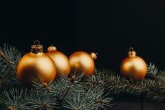 För leksakgarneringar för jul eller för nytt år guld- bollar och pälsträdfilial som är lantlig på träbakgrund, bästa sikt, kopier arkivfoto