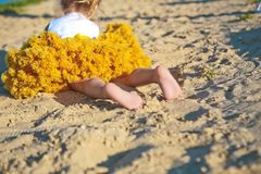 För liten flickasand för kjol gula frodiga häl för fot för strand royaltyfria foton