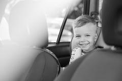 För litet barnpojke för stående lyckligt sammanträde i bilen Arkivfoton