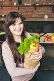 För livsmedelsbutikshopping för ung kvinna hållande påse med grönsaker som står i köket Royaltyfria Bilder