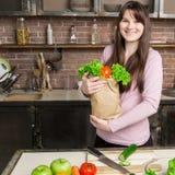 För livsmedelsbutikshopping för ung kvinna hållande påse med grönsaker som står i köket Royaltyfri Foto
