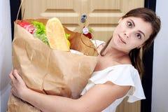 För livsmedelsbutikshopping för ung kvinna hållande påse med grönsaker Pappers- packe med livsmedelsprodukter i händer av kvinnah fotografering för bildbyråer