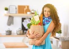 För livsmedelsbutikshopping för ung kvinna hållande påse med grönsaker som står i köket arkivfoto