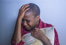 För livsstil stående inomhus av den unga ledsna och deprimerade svarta afro amerikanska kvinnan som sitter hemmastadd desperat go royaltyfri fotografi