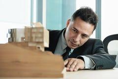 För Looking At Architecture för säker affärsman projekt miniatyrhus arkivfoton