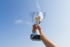 För mästarevinnare för idrottsman nen hållande övre kopp för trofé på himmelbakgrund Arkivbild