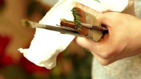 För målareinnehav för yrkesmässig konstnär borstar i henne hand som drar ett konstverk med olje- målarfärger stock video