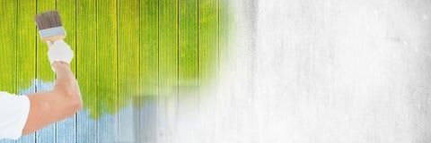 För målarfärgborste för målare hållande vägg för målning med övergång royaltyfri foto
