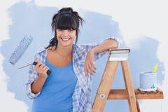 För målarfärgrulle för kvinna hållande benägenhet på stege arkivbild