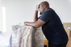 För möblemanghem för svart man rörande tungt begrepp för renovering royaltyfri bild