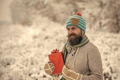 För manhåll för jul lycklig ask för gåva i snöig vinterskog royaltyfri fotografi