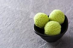För matchaglass för grönt te skopor på grå färgstenen fotografering för bildbyråer