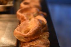 För matfotografi för makro nära övre bild av en linje av varma lagade mat yorkshire puddingar och mörk suddighetsbakgrund royaltyfria foton