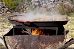 ` För matlagning`-paella, typisk spanjormaträtt, i skogen Arkivfoto
