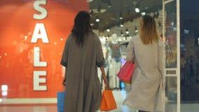 För meddelandebanret för två unga kvinnor försäljningen att underteckna in shoppar Arkivfoton