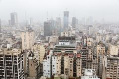 För Microcentro för område Buenos Aires för central affär horisont skyskrapor i vinter under molnig ledningshimmel i tung dimma A royaltyfri fotografi