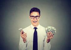 För mobiltelefon- och pengardollar för upphetsad lycklig yrkesmässig affärsman hållande kassa royaltyfri foto
