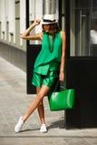 För modesommar för den stilfulla unga flickan poserar den iklädda gröna dräkten, den vita hatten och vita gymnastikskor i gatan p royaltyfri bild