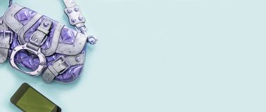 För modetillbehör för baner modernt ljus för grej för telefon för handväska för unga kvinnor - blått bakgrundskopieringsutrymme royaltyfria bilder
