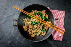 För mongoliannötkött för traditionell kines småfisk för uppståndelse i kinesiskt gjutjärn wokar med matlagningpinnar, sten kritis arkivfoto
