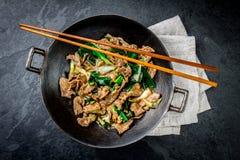 För mongoliannötkött för traditionell kines småfisk för uppståndelse i kinesiskt gjutjärn wokar med matlagningpinnar, sten kritis arkivfoton