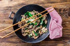 För mongoliannötkött för traditionell kines småfisk för uppståndelse i kinesiskt gjutjärn wokar med matlagningpinnar, träbakgrund arkivfoton