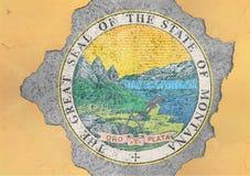 För Montana för USA-stat flagga skyddsremsa i stort konkret sprucket hål och brutet material arkivbild