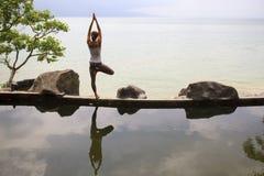 För morgonmeditation för kvinna praktiserande yoga på stranden arkivbild