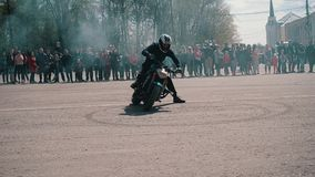 För motorcyklist som imponerande föreställning mycket driver och rotera i en cirkel som lämnar fotspår i asfalten Stort plan på s stock video