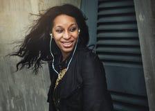 För musikmassmedia för den afrikanska kvinnan lurar lyssnande avkoppling för underhållning royaltyfri bild