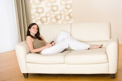 för musikspelare för holding home lyssnande kvinna för sofa Royaltyfri Bild