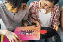 För musiktappning för vänner lyssnande begrepp för rekord royaltyfri fotografi