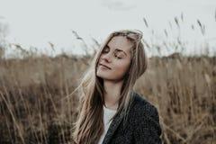 För mycket härlig och mode flicka med stängda ögon som står på sävbakgrund royaltyfri bild