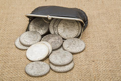 För mynthandväska för silverdollar spilld bakgrund Royaltyfria Foton