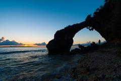 För naturlig stenig strand brosolnedgång för Silhouette Arkivbild