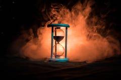 för objekttid för bakgrund begrepp isolerad white Konturn av timglasklockan och rök på mörk bakgrund med varm gul orange röd blå  Royaltyfri Bild