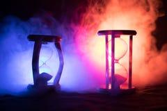 för objekttid för bakgrund begrepp isolerad white Konturn av timglasklockan och rök på mörk bakgrund med varm gul orange röd blå  Royaltyfri Fotografi