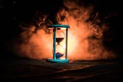 för objekttid för bakgrund begrepp isolerad white Konturn av timglasklockan och rök på mörk bakgrund med varm gul orange röd blå  Royaltyfri Foto