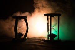 för objekttid för bakgrund begrepp isolerad white Konturn av timglasklockan och rök på mörk bakgrund med varm gul orange röd blå  Fotografering för Bildbyråer