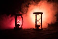 för objekttid för bakgrund begrepp isolerad white Konturn av timglasklockan och rök på mörk bakgrund med varm gul orange röd blå  Arkivfoto