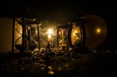 för objekttid för bakgrund begrepp isolerad white Kontur av ett mananseende mellan timglas med rök och ljus på en mörk bakgrund Royaltyfri Foto