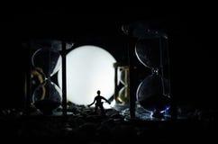 för objekttid för bakgrund begrepp isolerad white Kontur av ett mananseende mellan timglas med rök och ljus på en mörk bakgrund Arkivbild