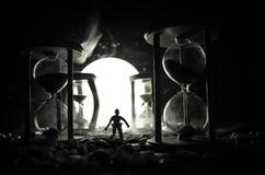 för objekttid för bakgrund begrepp isolerad white Kontur av ett mananseende mellan timglas med rök och ljus på en mörk bakgrund Arkivfoton