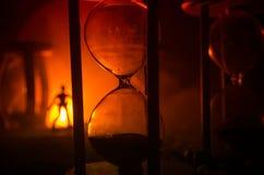 för objekttid för bakgrund begrepp isolerad white Kontur av ett mananseende mellan timglas med rök och ljus på en mörk bakgrund Royaltyfria Foton